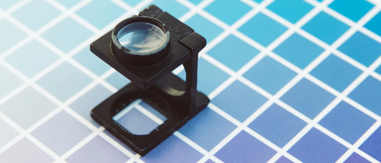 printing tips for graphic designers: checking colors with magnifying glass