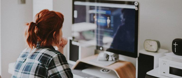 woman thinking behind computer