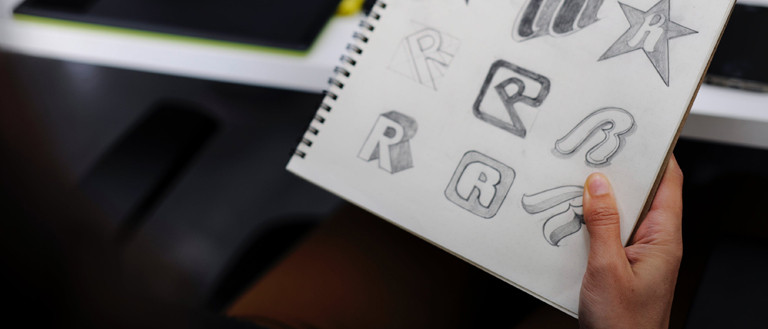 sketching a logo on a paper