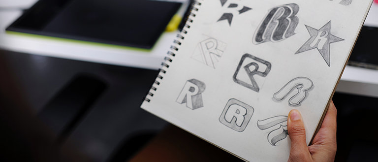 different logo sketches of R in a notepad
