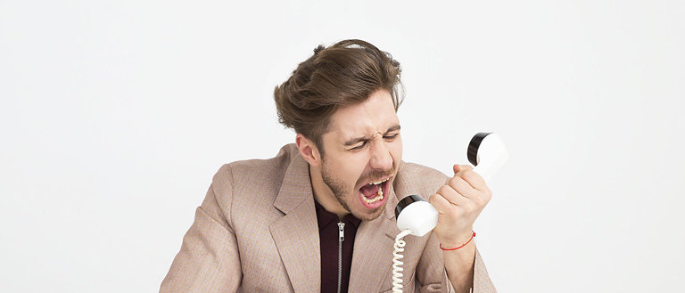 guy screaming into the phone: ways to deal with difficult graphic design clients featured image